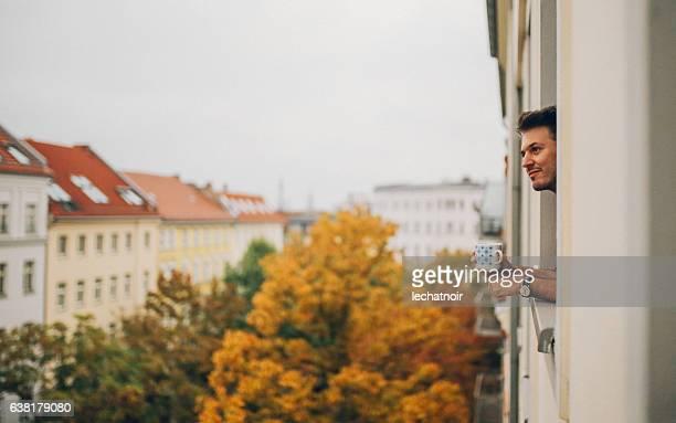 man looking through the apartment window in berlin prenzlauer berg - kleinstadt stock-fotos und bilder