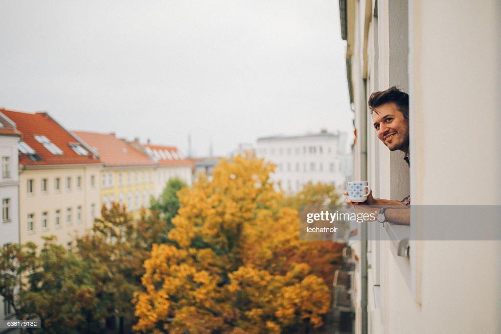 ベルリン・プレンツラウアー・ベルクのアパートの窓から見ている男 : ストックフォト