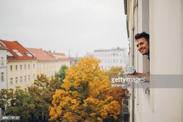 man looking through the apartment window in berlin prenzlauer berg - wohnung stock-fotos und bilder