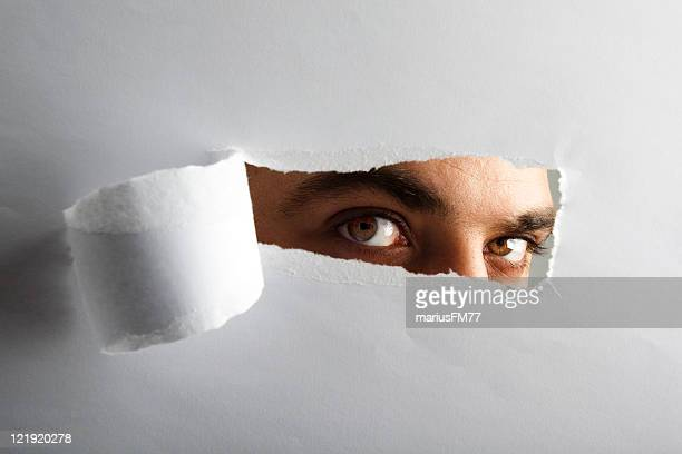 man looking through torn paper - lech stock photos and pictures