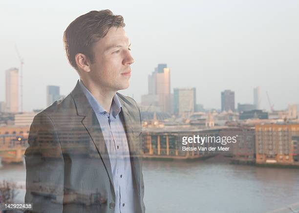 Man looking through window over city scape.