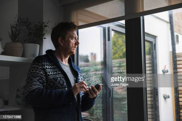 man looking through window - anxiety stock pictures, royalty-free photos & images