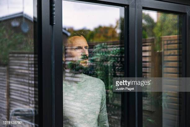 man looking through window - loneliness stock pictures, royalty-free photos & images