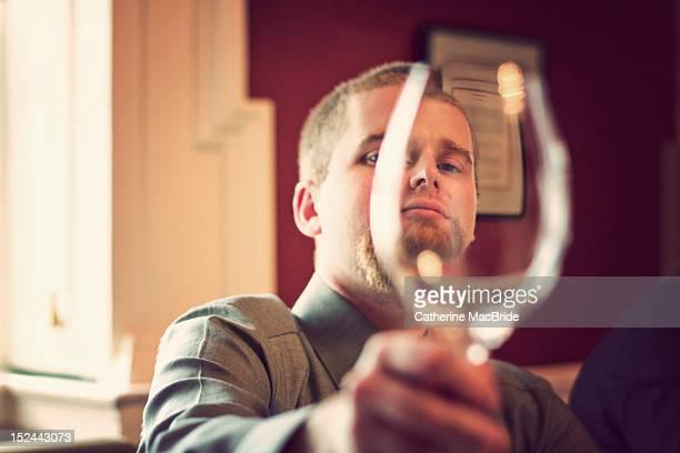 man looking through wine glass - catherine macbride stock-fotos und bilder