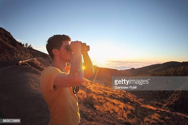 Man looking throuht binoculars at sunset