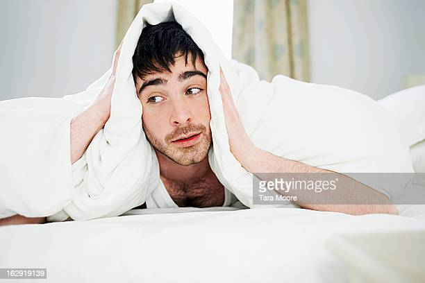 man looking tired in bed under covers