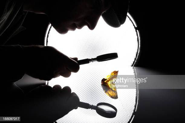 Man looking to an amber diamond through a magnifying glass