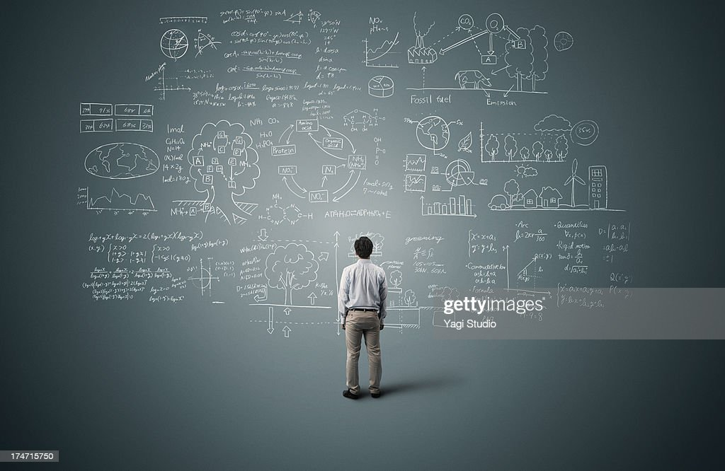 Man looking to formula and picture on blackboard : Stock Photo