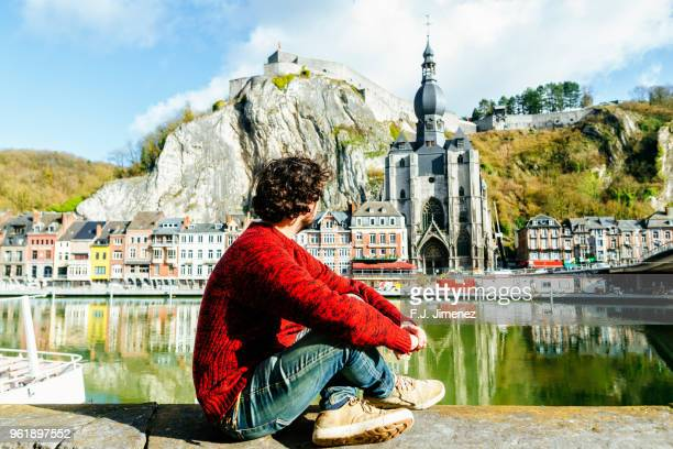 man looking towards dinant village in belgium - toerisme stockfoto's en -beelden