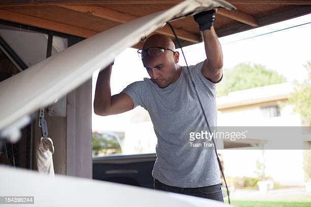 man looking under hood of car