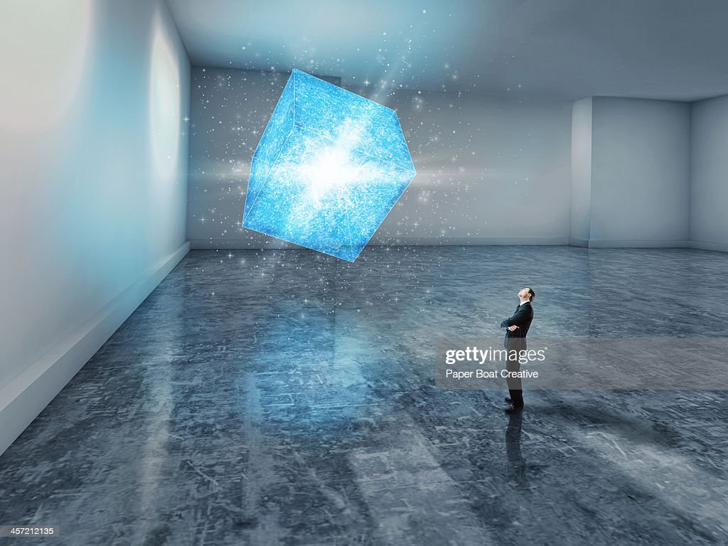 man looking up at a glowing blue 3D cube : ストックフォト