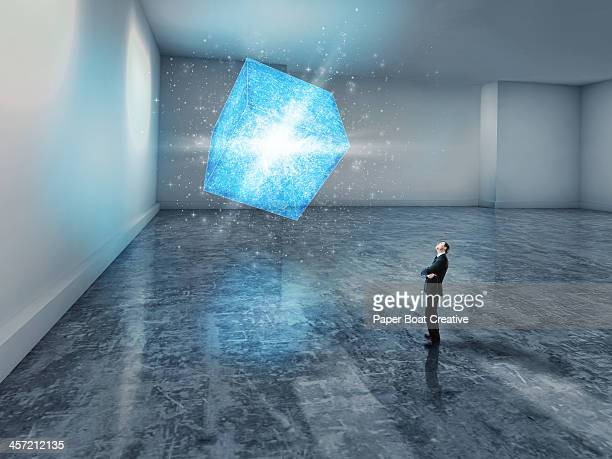 man looking up at a glowing blue 3d cube - calculating stock pictures, royalty-free photos & images