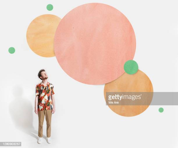 man looking up at cut out circles - only men stock pictures, royalty-free photos & images
