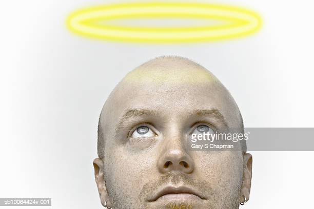 Man looking up at halo above head, close-up (Digital Composite)