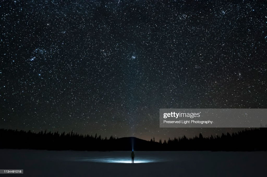 Man looking up at Pleiades star cluster and Orion constellation, Nickel Plate Lake, Penticton, British Columbia, Canada : Stock Photo