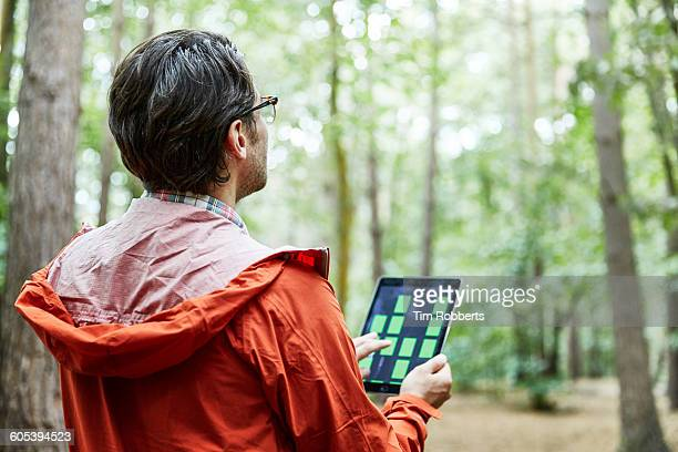 Man looking up with tablet in forest