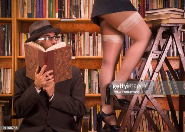 man looking up woman's skirt in library - beautiful legs in high heels stock photos and pictures