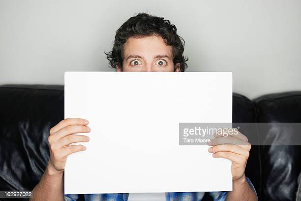 man looking wide-eyed holding blank sign - placard stock pictures, royalty-free photos & images
