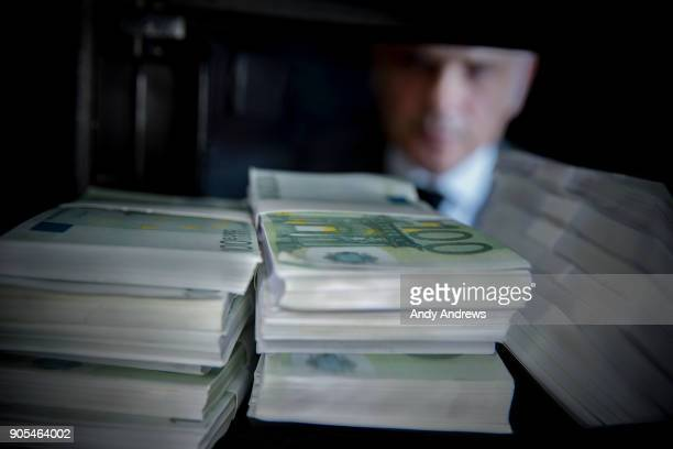 POV Man lookning at stacks of Euros in a safe