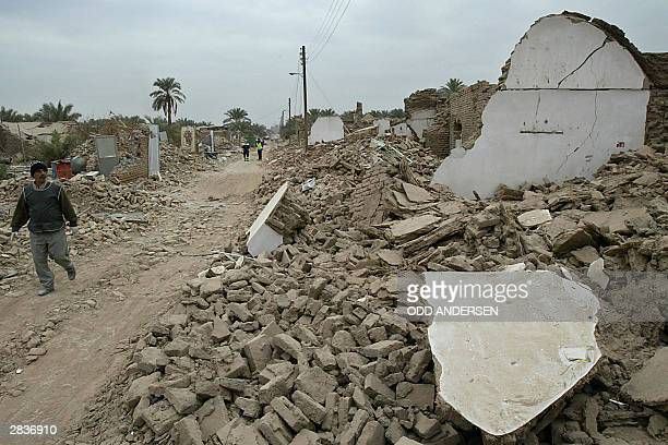 A man looks 30 December 2003 at the debris of houses flattened by last week's devastating earthquake in the southeastern Iranian city of Bam As many...