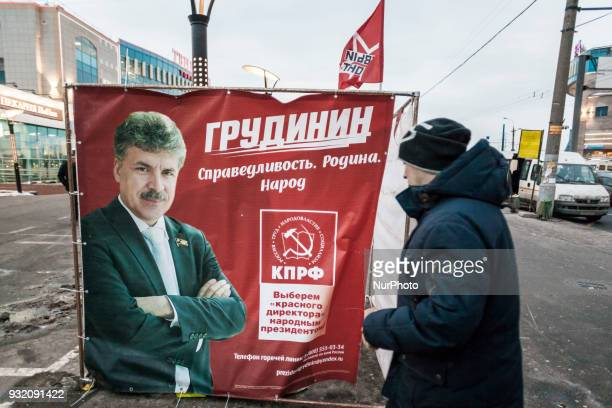 Man looks a banner of the official candidate of the Communist party Pavel Grudini in the streets of Moscow Russia on 14 March 2018 during the...