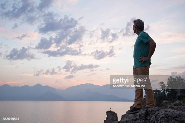 Man looks across bay to mountains at dusk