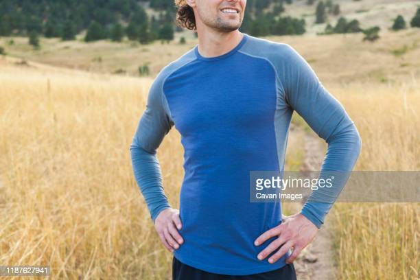 man looks around while on trail run in bear canyon, boulder, colorado - long sleeved stock pictures, royalty-free photos & images