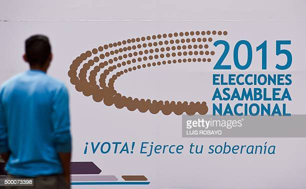 A man looks at a banner around the National Electoral Council headquarters in Caracas on December 5 2015 For the first time in 16 years of...