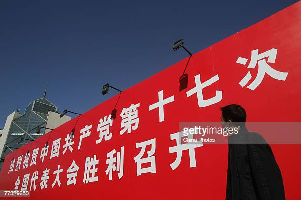 Man looks at a banner marking the opening of 17th National Congress of the Communist Party of China , at the Xidan shopping area on October 15, 2007...