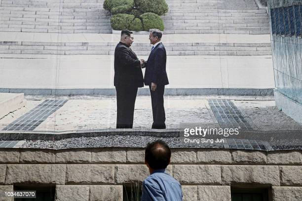 A man looks at a banner showing South Korea President Moon Jaein and North Korean leader Kim Jong Un to support the upcoming interKorean summit on...