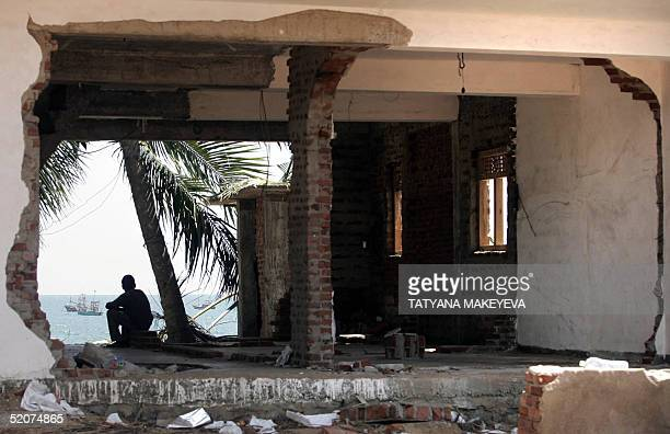 A man looks at a beach sitting in the tsunami partly destroyed house in Hambantota 250 km south of Colombo 28 January 2005 According to latest...