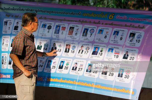 A man looks at a board with profiles of candidates during Thailand's general election in Bangkok