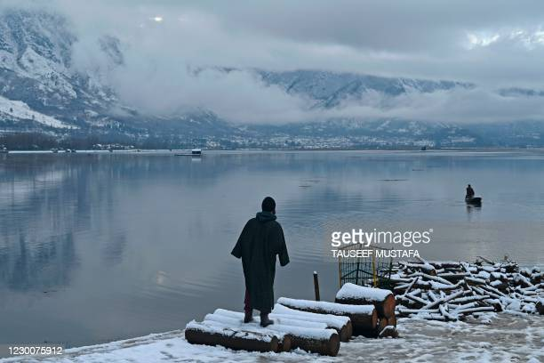 Man looks at a boatman steer a boat in Dal Lake after a fresh snowfall in Srinagar on December 12, 2020.