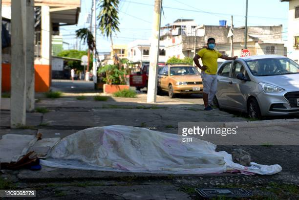 A man looks at a body said to be laying for three days oustide a clinic in Guayaquil Ecuador on April 3 2020 Troops and police in Ecuador have...