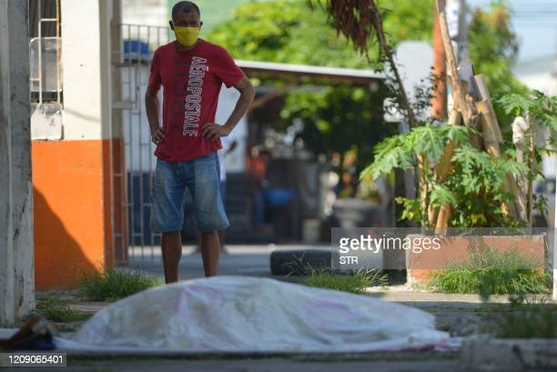 A man looks at a body said to be laying for three days outside a clinic in Guayaquil Ecuador on April 3 2020 Troops and police in Ecuador have...
