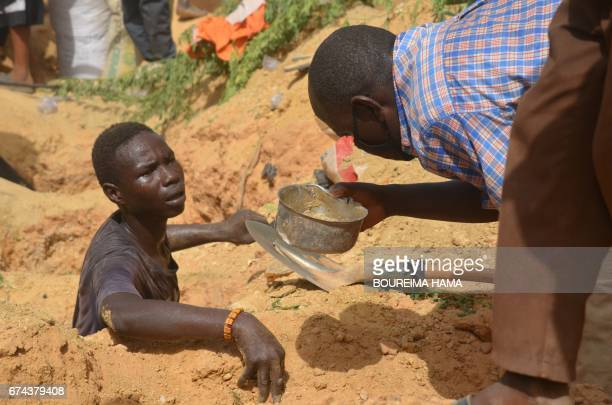 A man looks at a bowl near a digger searching gold on April 25 2017 in KafaKoira south of Niamey Hundreds of people sometimes whole families rush to...
