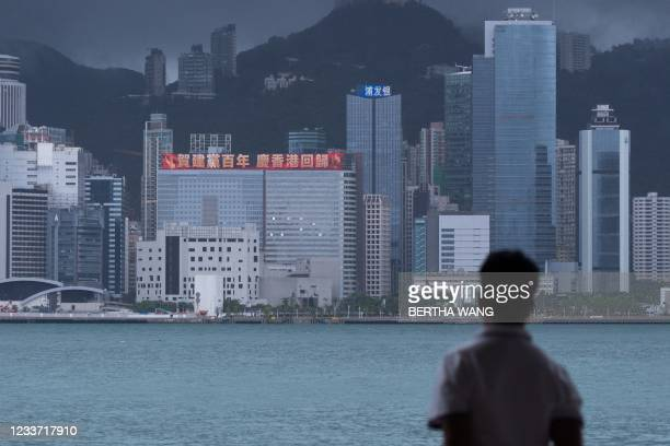 Man looks at a building with a LED billboard displaying a slogan celebrating the 100th anniversary of the Chinese Communist Party and the 24th...