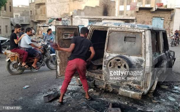 Man looks at a burnt car in Yemen's third city of Taez, on March 23, 2019. - Yemen's beleaguered Saudi-backed government and Iranian-linked Huthi...