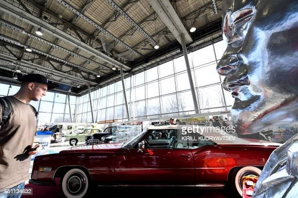 A man looks at a Cadillac Eldorado car of 1975 displayed next to a bust of Soviet Union's founder Vladimir Lenin as they visit an exhibition of 50...