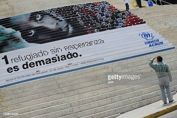 """Man looks at a campaign image of a refugee placed by the UN High Commission for Refugees in Caracas, on August 2, 2011. UNHCR is carrying out the """"A..."""