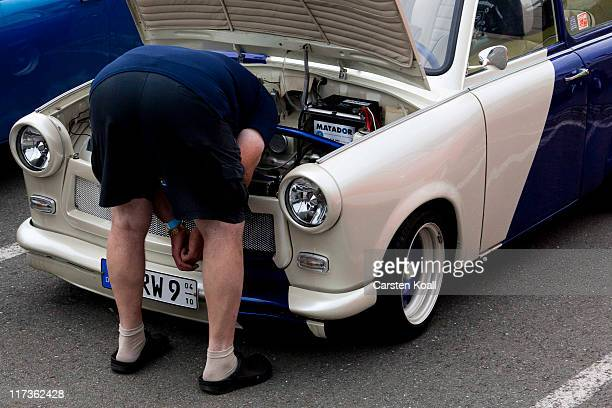 A man looks at a car as fans and owners of East Germanera Trabant cars gather at the 2011 International Trabantfahrer Treffen on June 25 2011 in...