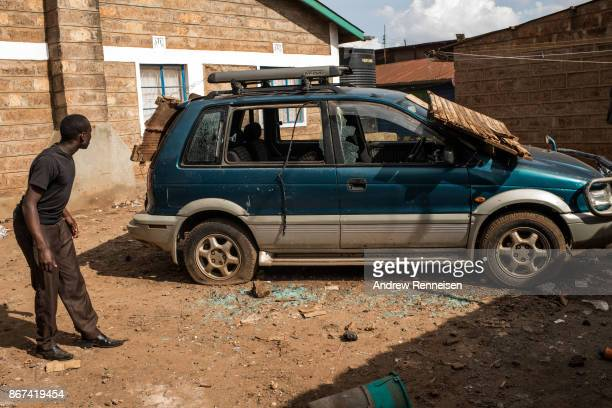 A man looks at a car which was destroyed after a group of men threw rocks and attempted to loot a residential compound in the Kawangware slum on...