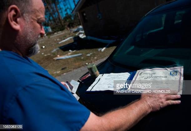 A man looks at a certificate of recognition from the Army that he was able to salvage from his damaged home in Port St Joe Florida on October 13...