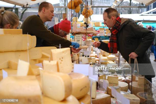 Man looks at a cheese before tasting at an organic farmers market near Northern Church on March 14, 2020 in Amsterdam, Netherlands.