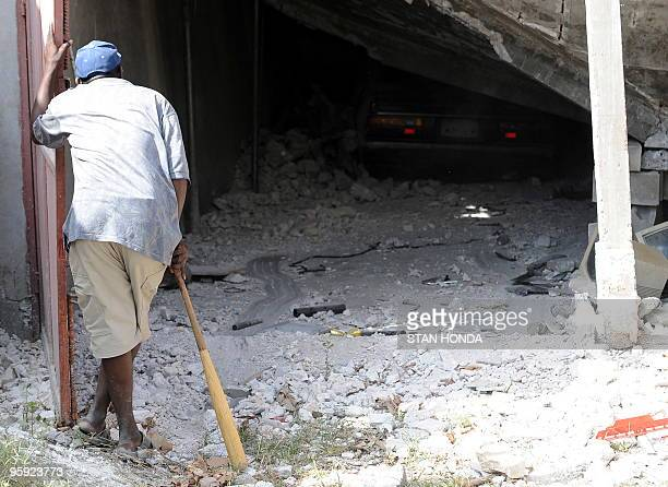 A man looks at a crushed car in Leogane on January 21 2010 following a devastating earthquake destroyed the city on January 12 Foreign medical teams...