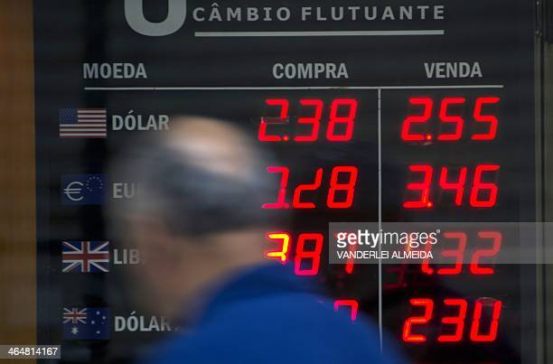 Man looks at a currency exchange bureau board announcing a rise of the US Dollar in relation with the Brazilian Real , in the financial district of...