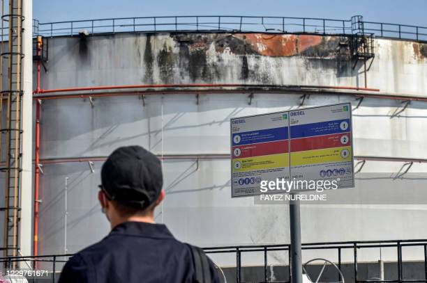 Man looks at a damaged silo a day after an attack at the Saudi Aramco oil facility in Saudi Arabia's Red Sea city of Jeddah, on November 24, 2020. -...
