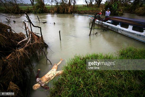 A man looks at a dead body as it floats in the river at the isolated village of Myasein Kan on May 20 2008 in the Ayeyarwaddy delta Myanmar It has...