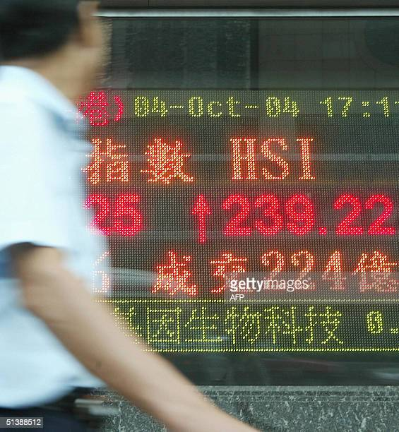 Man looks at a digital screen which shows a result of the Heng Seng Index closed up 239.22 points at 13,359.25 in Hong Kong on 04 October 2004. Hong...