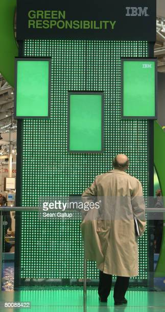 Man looks at a display advertising a more green-oriented philisophy at the IBM stand at the CeBIT technology fair a day before the fair's official...